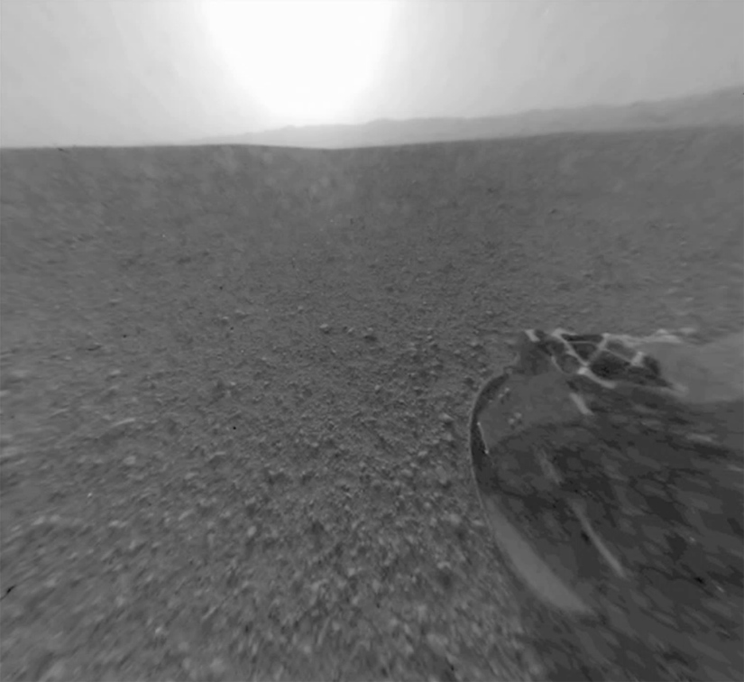 The view from the rover's rear hazcam, featuring the rim of Gale Crater and the light of a setting Martian Sun. Credit: NASA/JPL-Caltech
