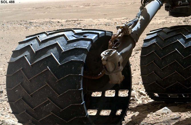 Curiosity's right-middle and rear wheels, bearing the scars of 488 sols of rough roving. Credit: NASA/JPL-Caltech